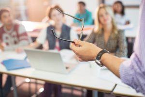 Professor gesturing with eyeglasses in classroom